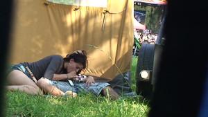 Un voyeur filme une brune qui se fait niquer derrière une tente